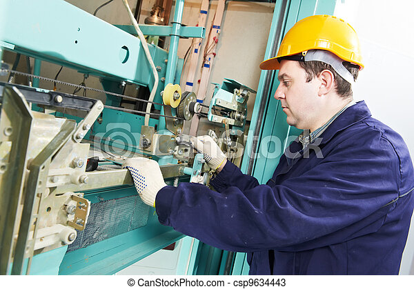 machinist with spanner adjusting lift mechanism - csp9634443