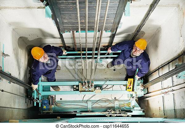 machinists adjusting lift in elevator hoist way - csp11644655