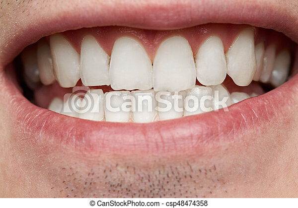 Macro of healthy man teeth. clean white human teeth in smile.