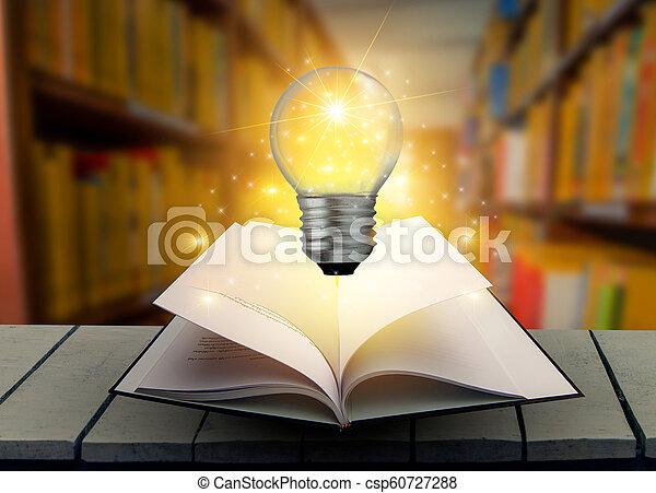 La bombilla está sobre la mesa. Madera en el libro de la biblioteca y la bombilla vieja en una mesa de madera leyendo por composición a la luz de las velas - csp60727288