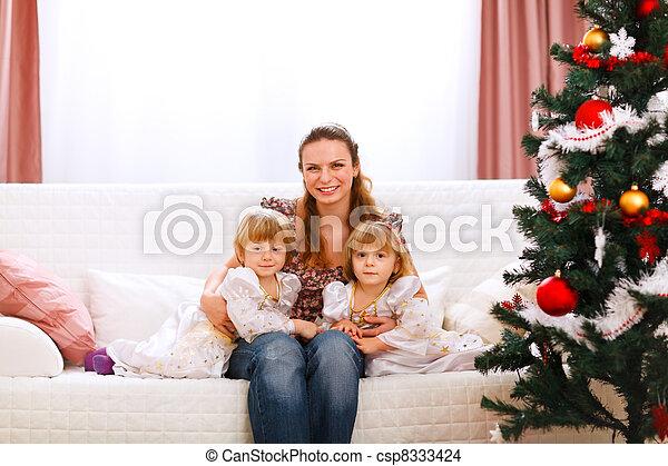 Retrato de madre con dos hijas gemelas cerca del árbol de Navidad - csp8333424