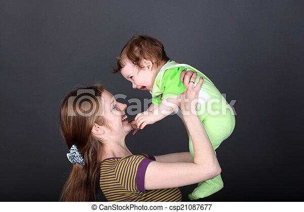 Retrato de madre feliz jugando con su lindo hijo - csp21087677