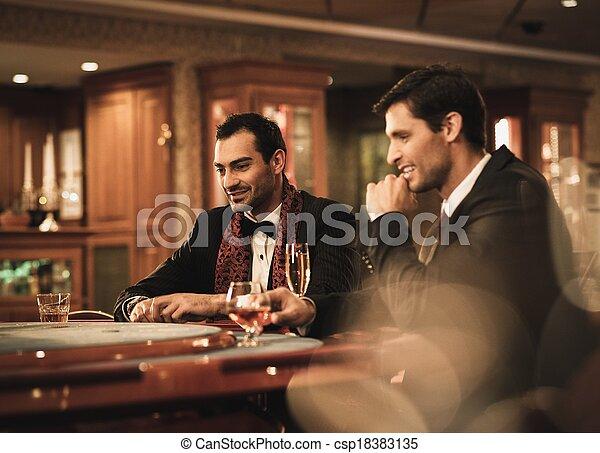 Zwei junge Männer in Anzügen hinter dem Spieltisch in einem Kasino - csp18383135