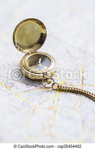 Magnetic compass on a blurry map - csp35454402