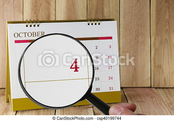 Magnifying glass in hand on calendar you can look Fourth date of month,Focus number four in October. - csp40199744