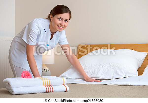 Maid making bed in hotel room - csp21536980