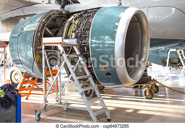 Maintenance, opened aircraft engine in the hangar in huge industrial hall - csp64973285