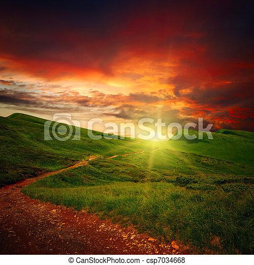 Majestätischer Sonnenuntergang und Pfad durch eine Wiese - csp7034668
