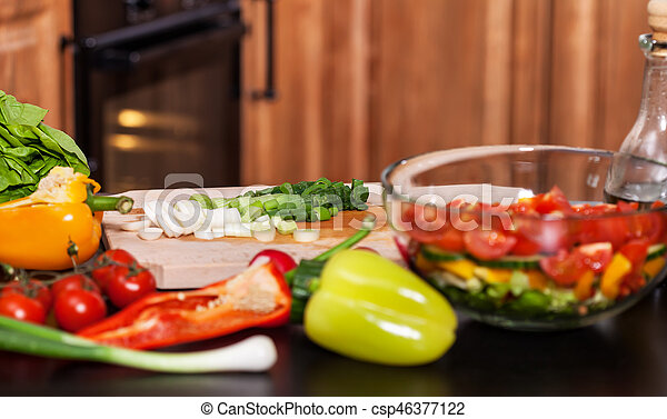 Making a fresh vegetables salad - chopping the spring onions - csp46377122