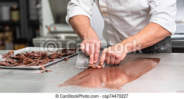 Making handmade chocolates. A confectioner making chocolate sweets. Close-up. - csp74470227