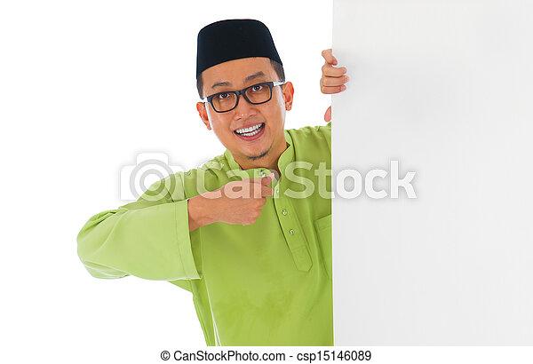 malay male with blank card during hari raya Eid al-Fitr aidilfitri celebration   - csp15146089