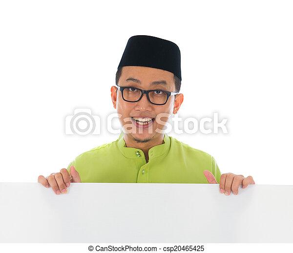 malay male with blank card during hari raya Eid al-Fitr aidilfit - csp20465425