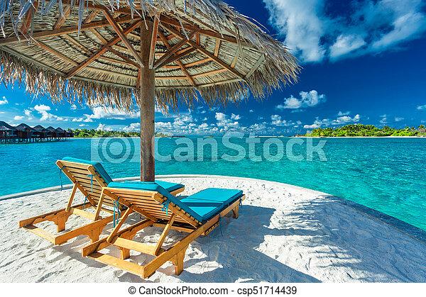 Dos sillas de playa bajo paraguas con vista al océano en Maldivas - csp51714439