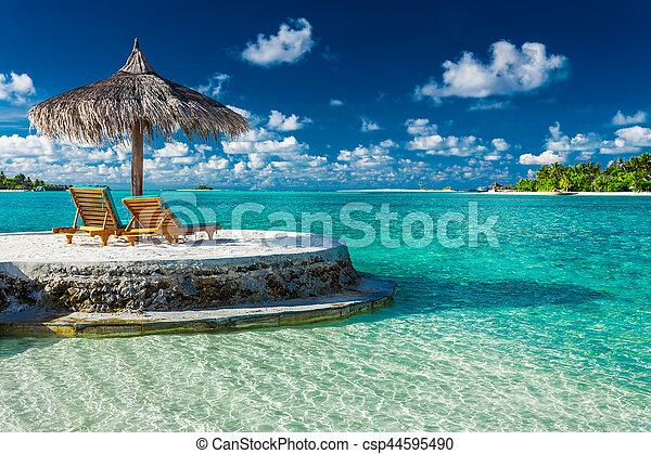 Dos sillas de playa bajo paraguas con vista al océano en Maldivas - csp44595490