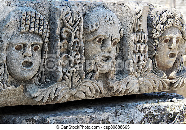 Male and female theatrical mask carved on stone surface - csp80888665