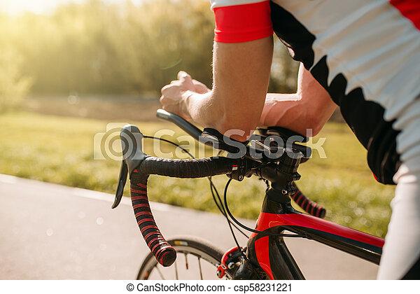 Male bycyclist in sportswear, cycling on bike path - csp58231221