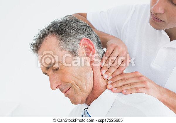 Male chiropractor massaging patients neck - csp17225685