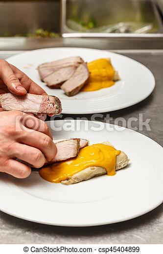 Male cooks preparing meals - csp45404899