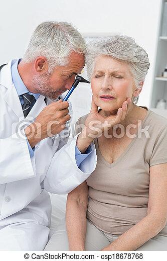Male doctor examining senior patient's ear - csp18678768