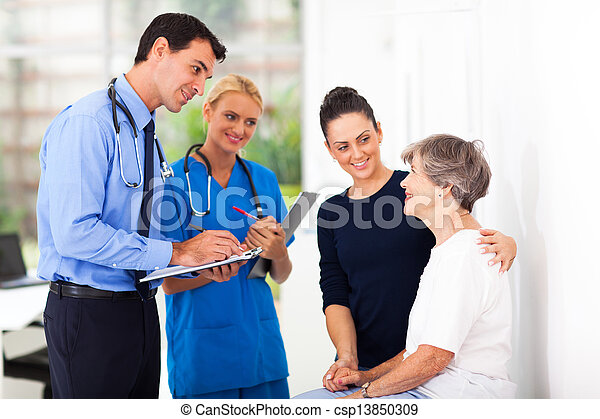 male doctor writing medical prescription for senior patient - csp13850309