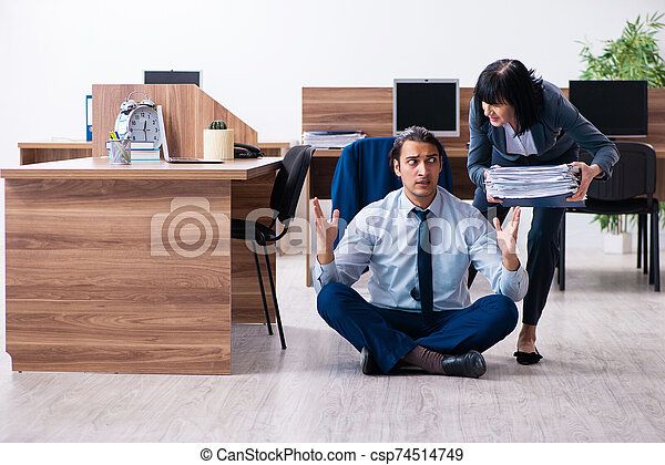 male employee doing yoga exercises in the office the male