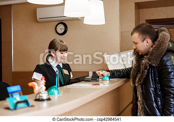 Male guest at hotel reception  during check-in - csp42984541