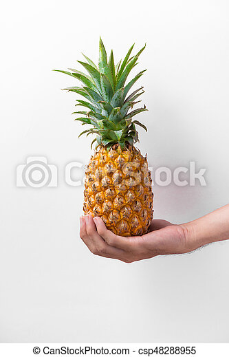 Male hand holding a pineapple isolated on white. - csp48288955