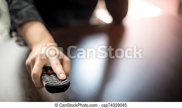 Male hand holding TV remote control - csp74329045