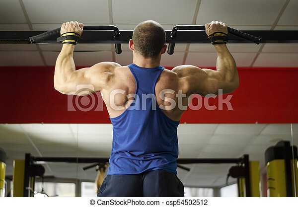 Male heavyweight athlete doing pull-ups, perfect masculine body, healthy life - csp54502512