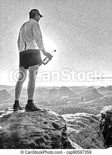 Male hiker athlete on a rock during a trail in the mountains, far view of the region. - csp90597359