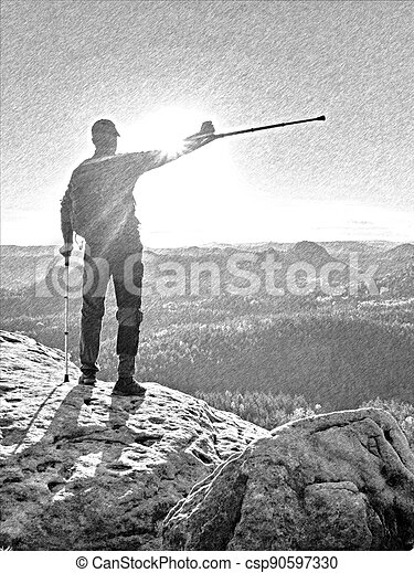 Male hiker athlete on a rock during a trail in the mountains, far view of the region. - csp90597330