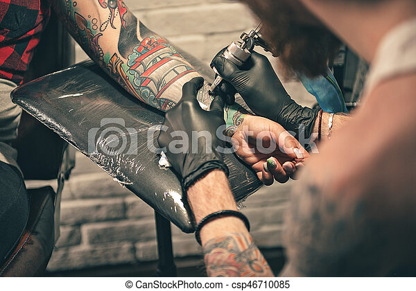 Male in gloves doing tattoo on hand - csp46710085
