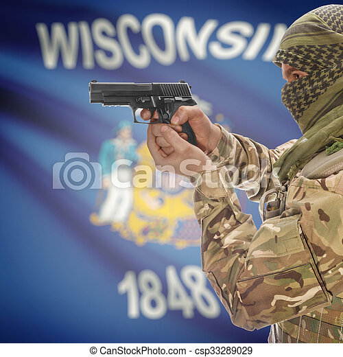 Male in muslim keffiyeh with gun in hand and flag on background - Wisconsin - csp33289029