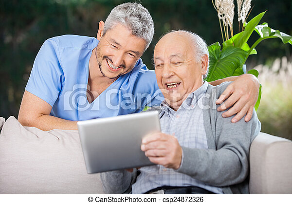 Male Nurse And Senior Man Laughing While Looking At Digital PC - csp24872326