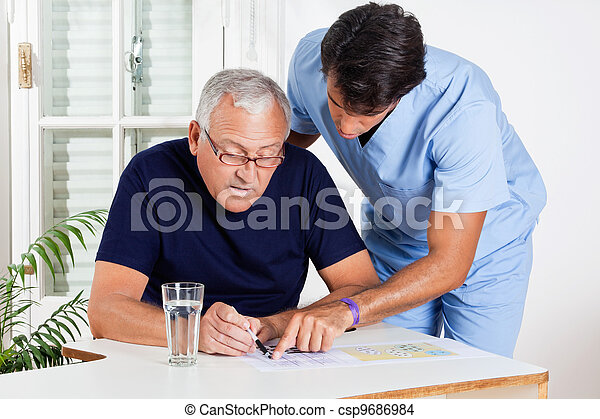 Male Nurse Helping Senior Man In Solving Puzzle - csp9686984