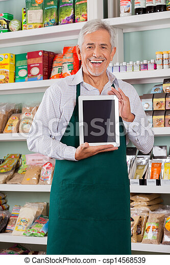 Male Owner Showing Digital Tablet In Store - csp14568539