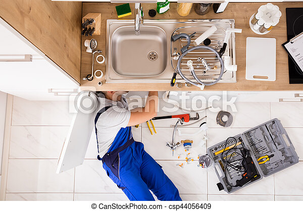 High angle view of male plumber in overall fixing sink pipe stock ...