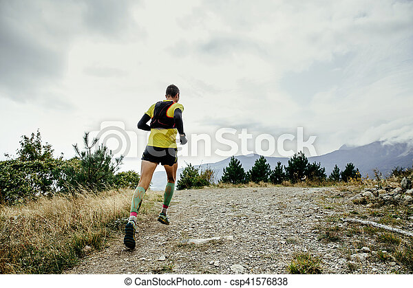 72016020ef Male runner in compression socks and backpack running a mountain ...