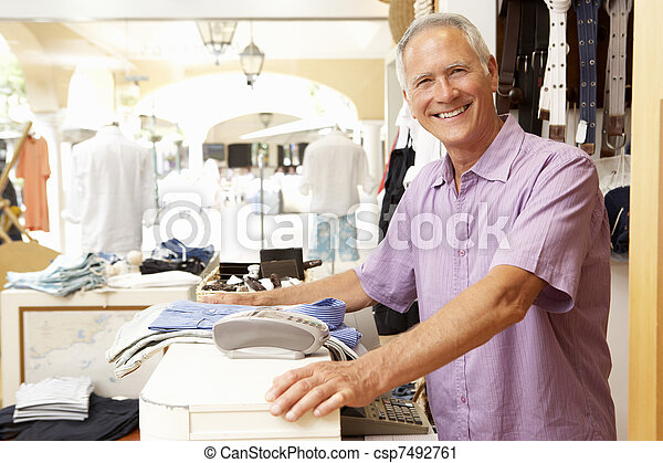 Male Sales Assistant At Checkout Of Clothing Store - csp7492761