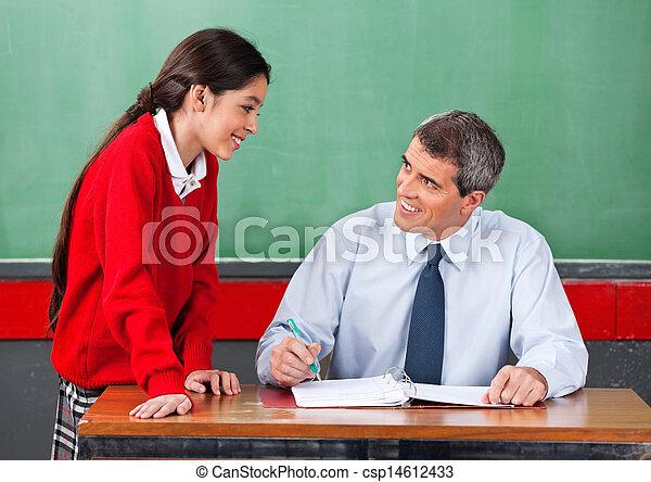 Male Teacher Discussing With Schoolgirl At Desk Csp14612433