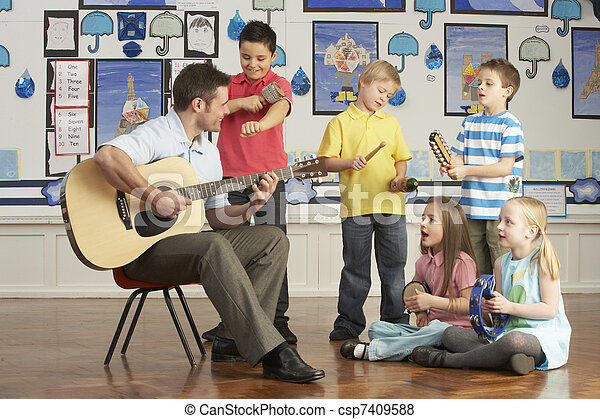 Male Teacher Playing Guitar With Pupils Having Music Lesson In Classroom - csp7409588
