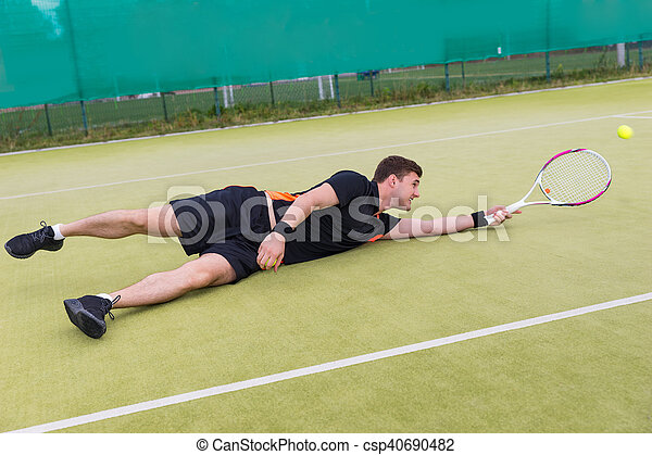 Male tennis player in action during the game fallen on a court - csp40690482