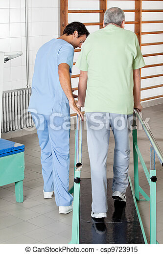 Male Therapist Assisting Senior Man To Walk With The Support Of - csp9723915