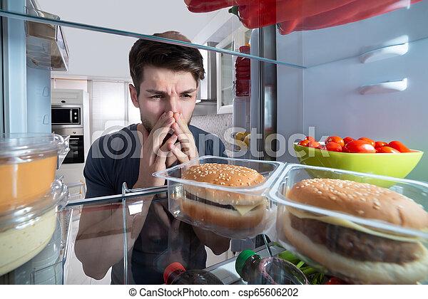 El hombre reconoce el mal olor del refrigerador - csp65606202