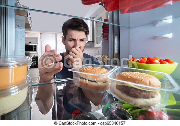 El hombre reconoce el mal olor del refrigerador - csp65340157