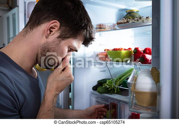 El hombre reconoce el mal olor del refrigerador - csp65105274