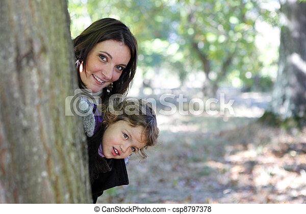 Mamá y su hija se esconden detrás de un árbol - csp8797378
