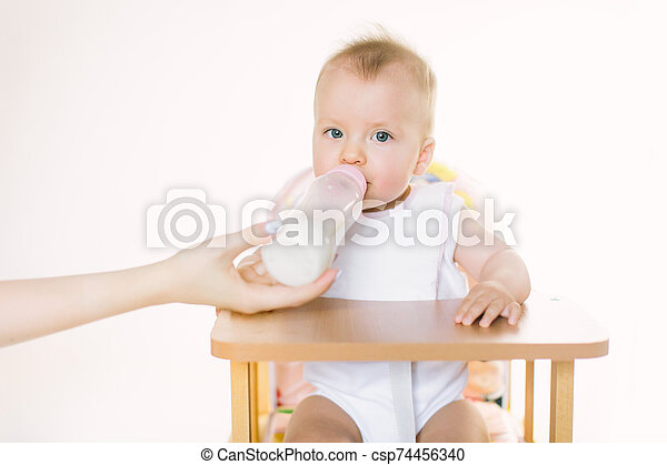 Mama's hand feeds the baby out of the bottle. The child is seated in a chair on a white background - csp74456340