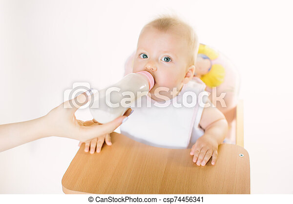 Mama's hand feeds the baby out of the bottle. The child is seated in a chair on a white background - csp74456341