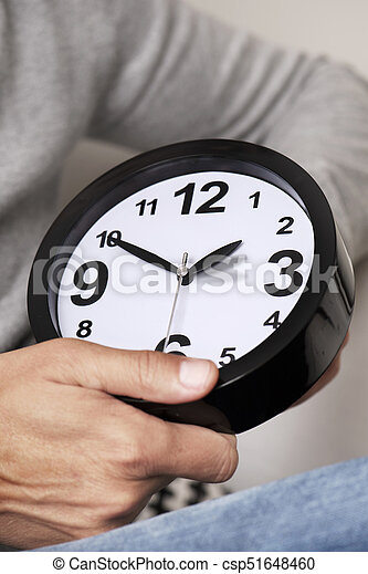 man adjusting the time of a clock - csp51648460